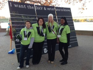 Students stand in front of display board at DAV 5K