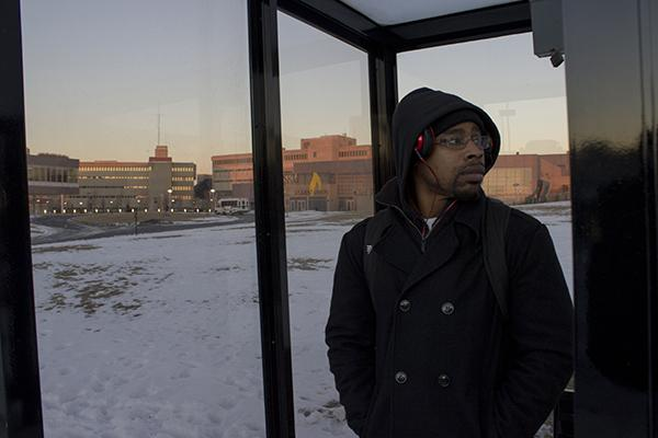 Patrick Pugh, EMB senior, waits outside in freezing temperatures for a bus.