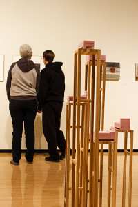 Artwork surrounds students viewing the main art gallery.