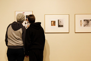 Two students view faculty member's photographs as part of the current art exhibition.