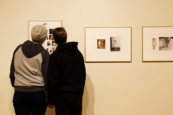 Two students view faculty members photographs as part of the current art exhibition.