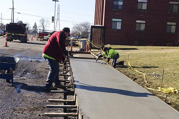 Worker lays down concrete outside of Callahan Hall.