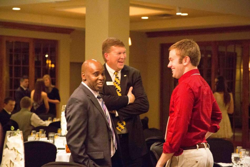 Dean Jeffrey Waple and Peter Gitau, vice president of Student Affairs talk with a member of the Homecoming 2014 court.