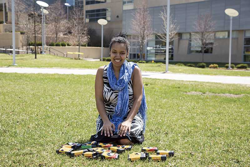 Senior studio arts major Lwam Eyassu with some of the disposable cameras used for her 100 Voices project.