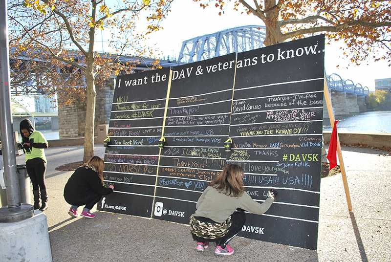 Participants write messages to veterans with chalk on Savicki's wall.