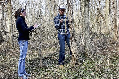 Environmental science major Katie Ollier records data with fellow researcher Freeman.