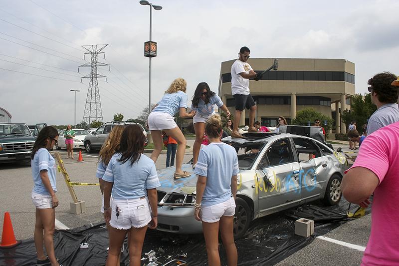 Delta Gamma sorority girls taking a swing at a car.