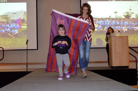 Best Buddies Vice President Summer Buchanan accompanies 4-year-old Ellie Hammond on the runway.