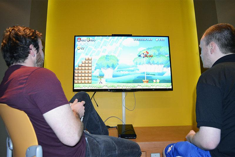 Two students play Super Smash Bros. U in the game room at NKU.