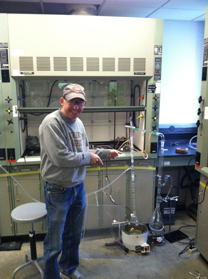 NKU Chemistry professor KC Russell poses with Matthew Miles' machine. Russell has been supporting Miles in the creation of the machine.