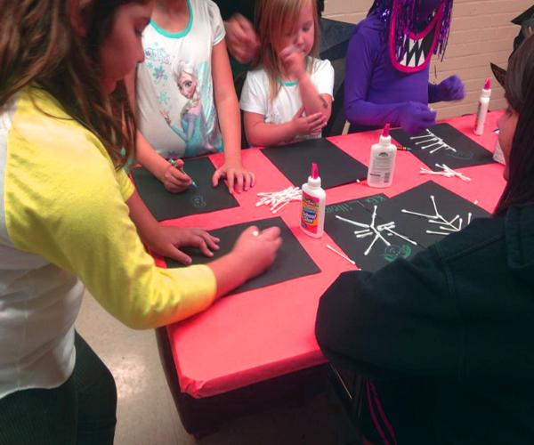 Community children and volunteer NKU makes cotton swab skeletons during Norse-O-Ween event.