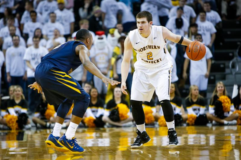 NKU men's basketball player Tayler Persons dribbles around a defender during the first half of NKU's 42-67 loss to West Virginia University. NKU was defeated by West Virginia University 42-67 at The Bank of Kentucky Center on Sunday, Dec. 7, 2014.