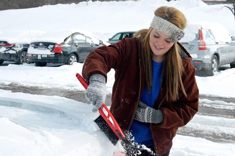 Freshman Diane Poe works to clear the snow off of her car this afternoon. NKU was closed Wednesday, Feb. 18 due to inclement weather.