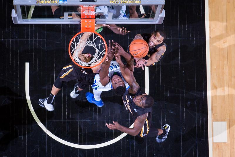 NKU guards Chad Jackson (top right), Tyler White (left) and center Jalen Billups (bottom right) struggle to rebound the ball against FGCU's Marc-Eddy Norelia (center) during NKU's 59-65 loss to FGCU. NKU lost to Florida Gulf Coast 59-65 at The Bank of Kentucky Center on Thursday, Feb. 12, 2015.