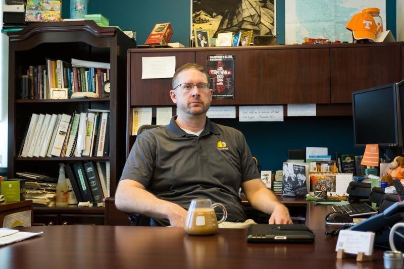 John Farrar sits in his office, which is decorated with collectibles from his travels.