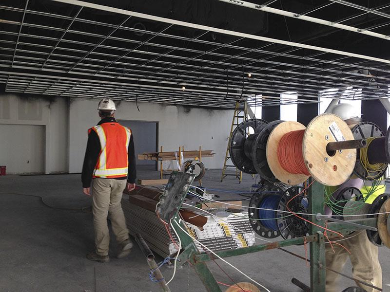 Project Manager JD Barnes leads the way through what will be a spinning room. SGA toured the site March 30.