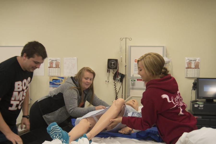 First-year nursing students (left to right) Anthony Roberts, Allison Fangman and Katie Golfman transfer a mannequin in a skills lab.