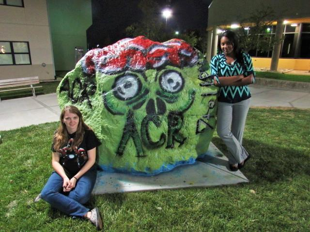 The VP and President of ACR, Brandy Brawner (left) and Dana Jetter (right) paint the spirit rock in front of Norse Commons hoping to get students excited for Callahans Haunted House, coming up on Oct. 29.
