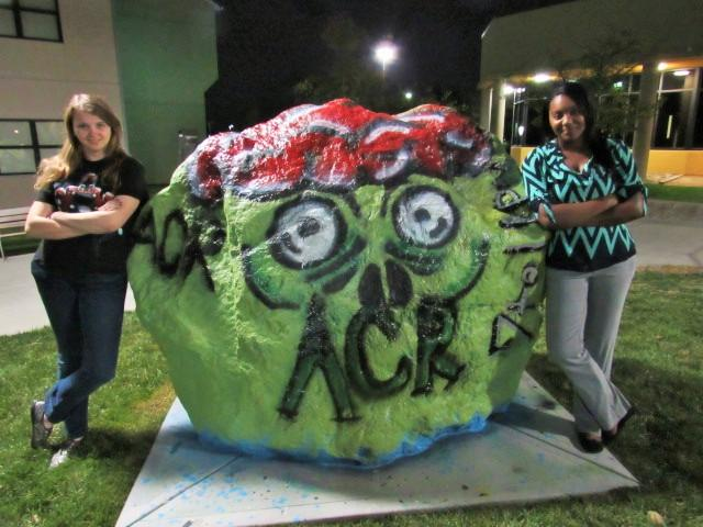 The VP of ACR, Brandy Brawner (left) and President, Dana Jetter (right) paint the spirit rock in front of Norse Commons advertising Callahans Haunted House on Oct. 29.
