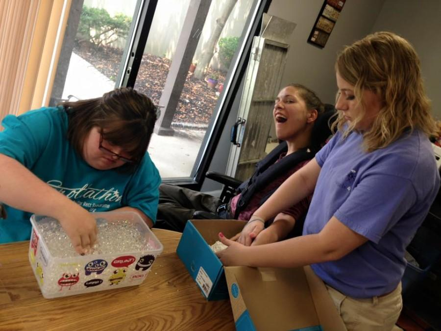 Justice working with Sarai and Toni on sensory activities - which help stimulate the use of their senses. Justice is helping Sarai with hand over hand to work on her sense of touch.