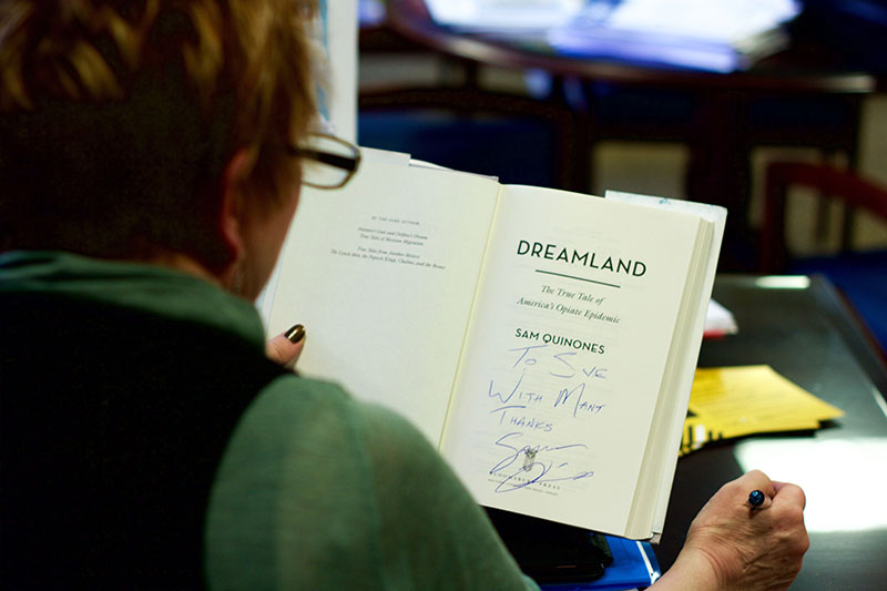 Provost Sue Ott Rowlands reviews her signed copy of