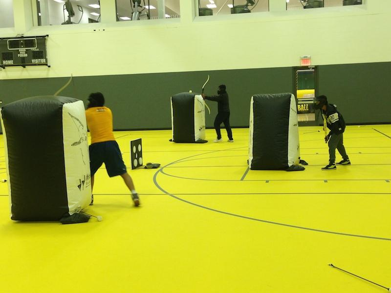 Students try to shoot their opponents while enjoying archery tag, one of the new activities for the homecoming festival.