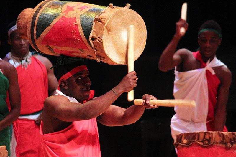 Burundian drummer performs while balancing a drum on his head