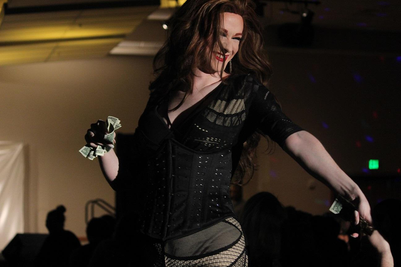 Mirelle Jane Divine collects dollar bills from the crowd as she performs.