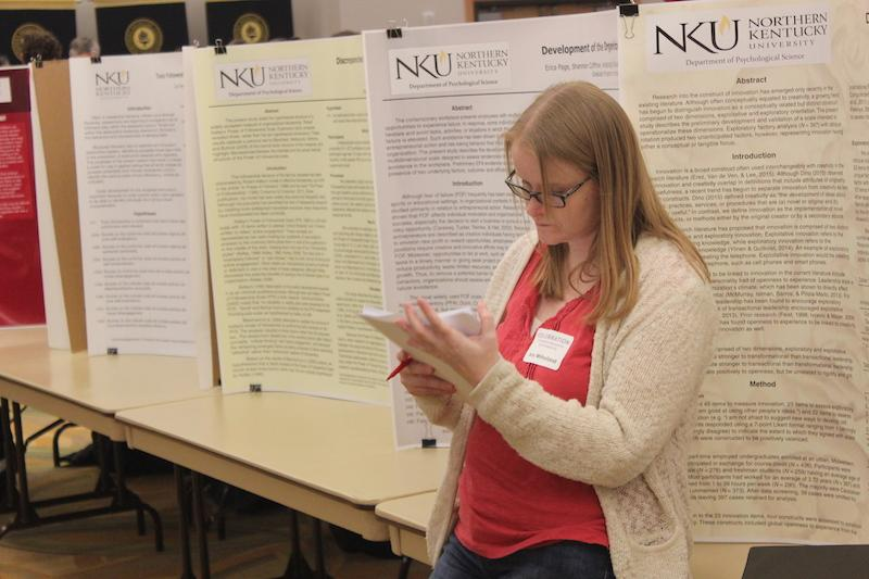 Participants, students and staff walk around to view others research findings and projects.