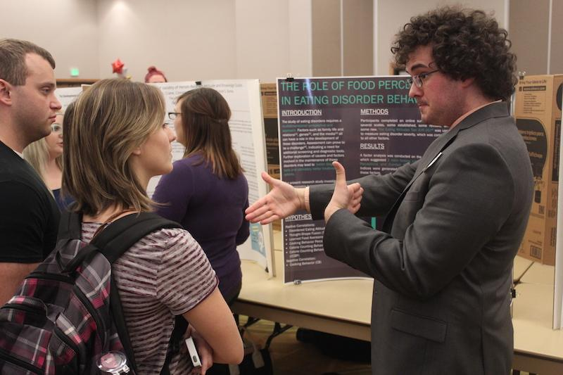 A student discusses their poster and research with others at the Celebration Poster event.