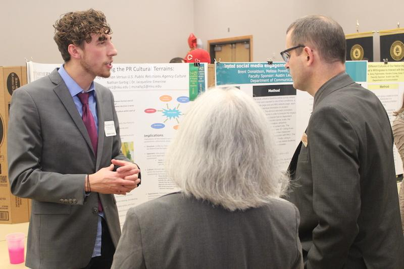 Nathan Garbig discusses his poster at the Celebration Festival with Zach Hart, co-chair of the event.