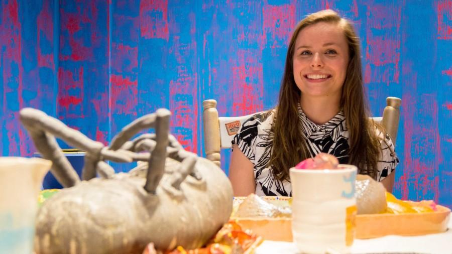 "Emma Clixby, BFA spatial arts major, tries to bring awareness with her exhibit ""Consumed."" Featuring a dining room with a sculpted food and plates, Clixby focuses on consumerism in America."