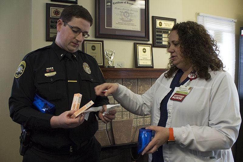 Ashel Kruetzkamp, nurse manager of the emergency department at St. Elizabeth in Edgewood, shows Lt. John Gaffin the contents of a naloxone kit. NKU officers were equipped with naloxone on April 1.