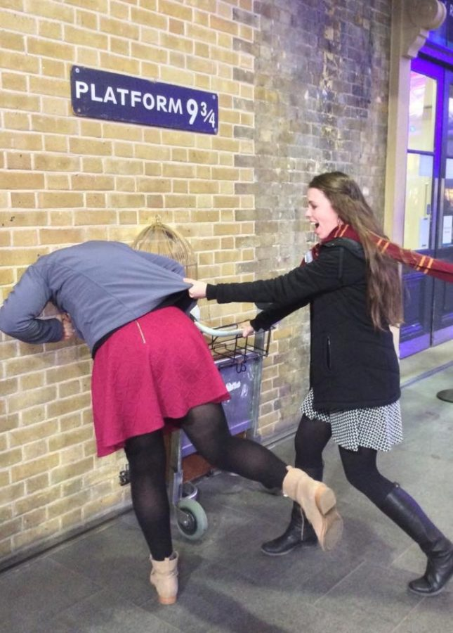 Two+students+pose+at+the+platform+9+3%2F4+entrance+at+the+train+station+in+London.+