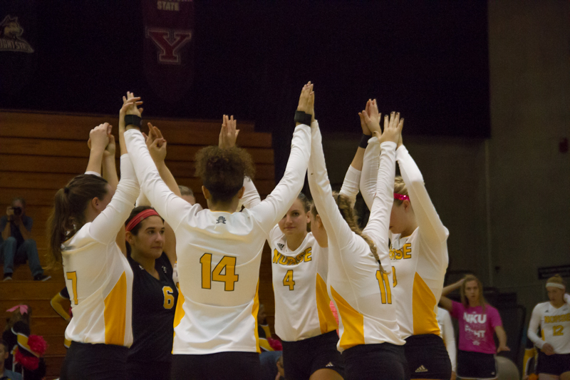 The Norse volleyball team raises their hands in celebration after scoring a point. Creamer (14) won Horizon League Offensive Player of the Week while Lauren Hurley (6) won Defensive Player of the Week.