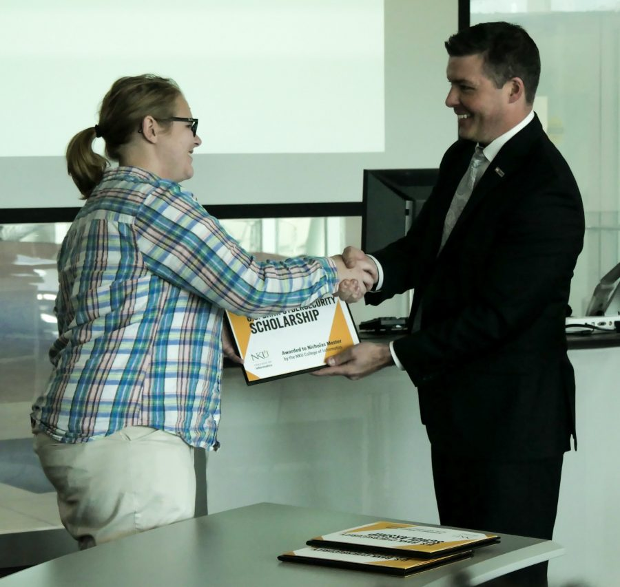 Allyson Frame (left) receives her scholarship from Jason Witty, US Bank executive vice president and chief information security officer.