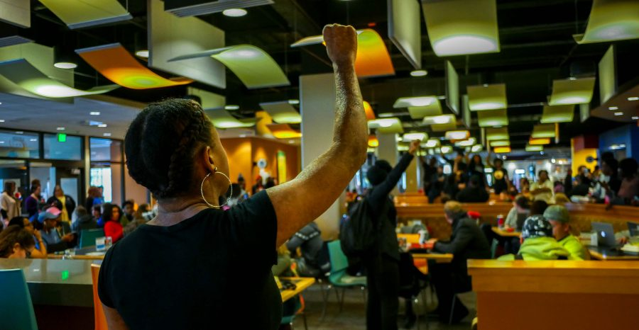 Tekiuh Hutton raises her fist in solidarity with The Unaddressed. Several students performed a spoken word demonstration in the SU.