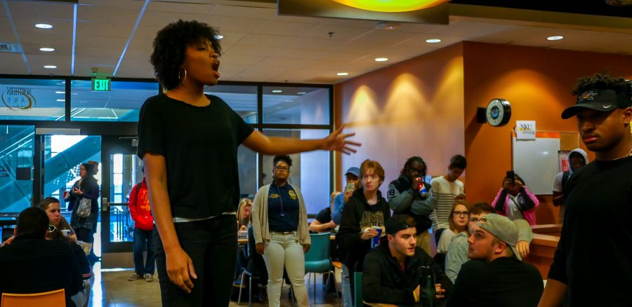 Briana Lee stood on a chair in the thick of the SU. The spoken word gets the conversation started, she said.