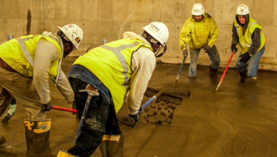 Workers+flatten+and+level+wet+cement+that+will+harden+to+be+the+building%27s+foundation.
