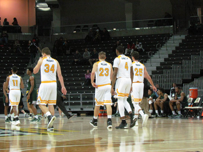 Drew McDonald (34), Carson Williams (23), Jeff Garrett (4), and Cole Murray (25) walk on to the court after a timeout.