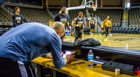 Brian Boos looks over the data from the Polar Pro on an iPad while the men's basketball team warm-ups for practice