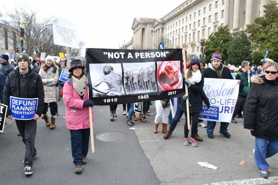 Protestors hold signs. The March took place in Washington, D.C.