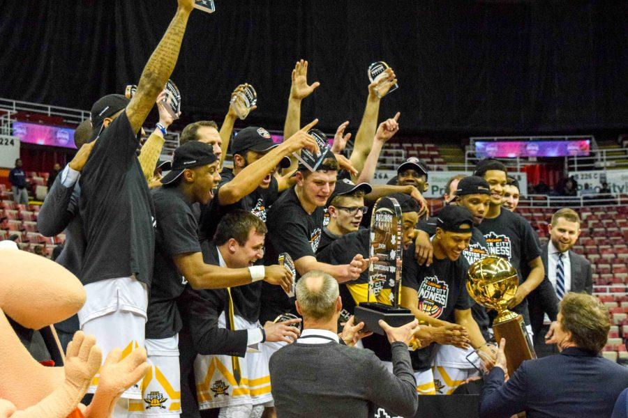 NKU AD Ken Bothof presents the Norse the Horizon League tournament championship trophy.