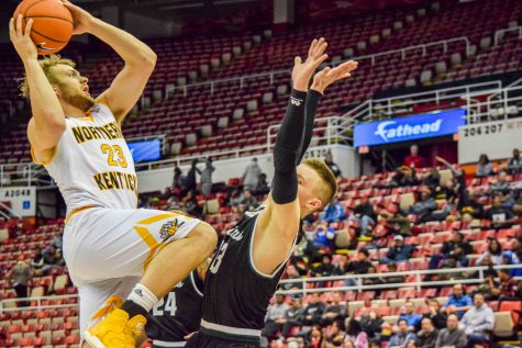 NKU's Carson Williams (23) goes up over Grant Benzinger (13) during Sunday's Horizon League quarterfinal game at Joe Louis Arena.