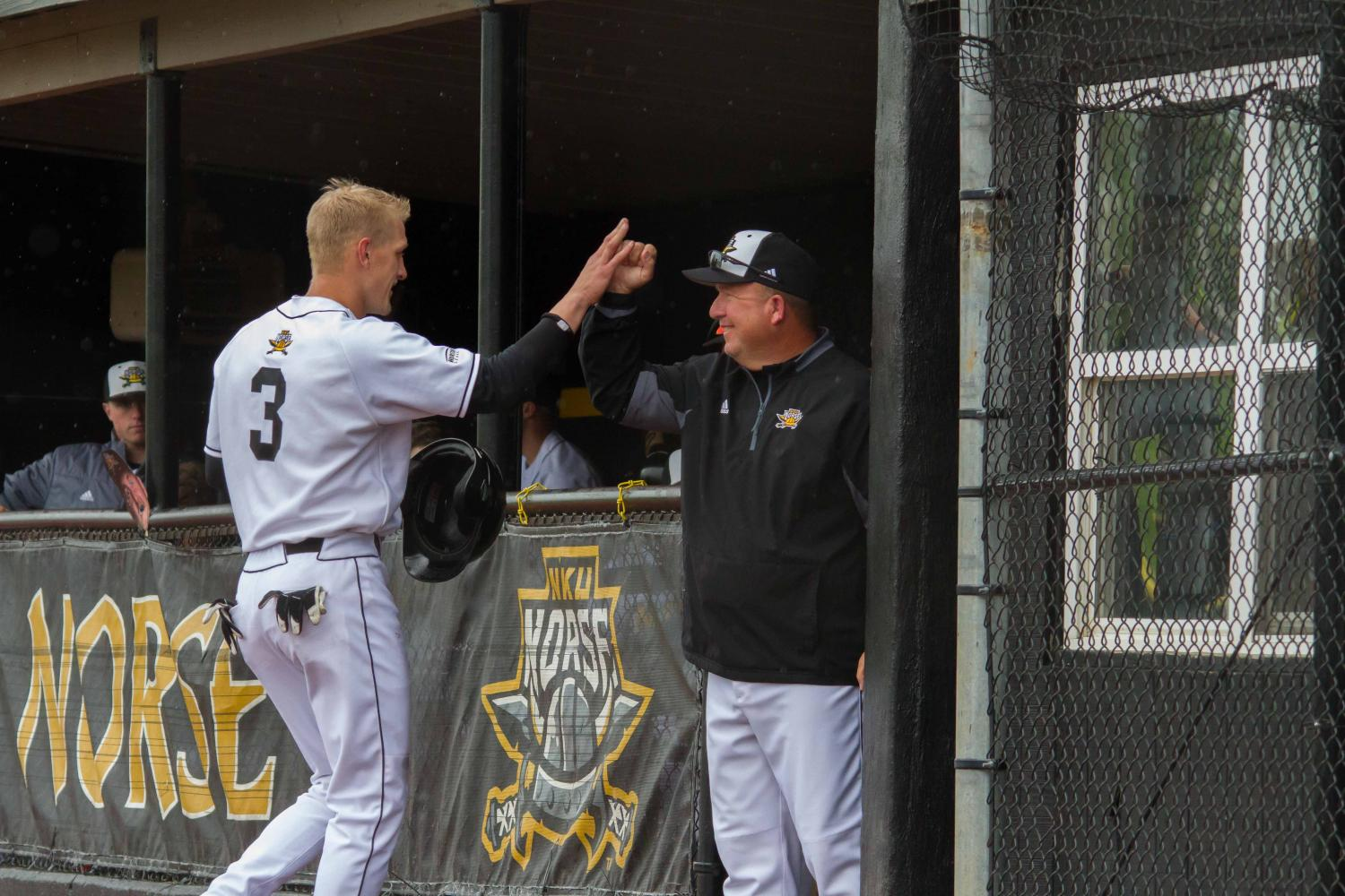 Coach Todd Asalon high fives Jake Richmond after Richmond scored a run against Oakland