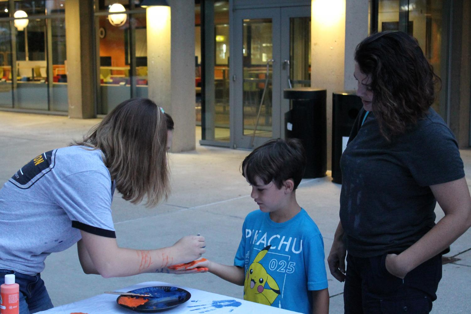 Community members, faculty, administration and  students turned out for the Vigil. Here, Edelen helps paint a child's hand.