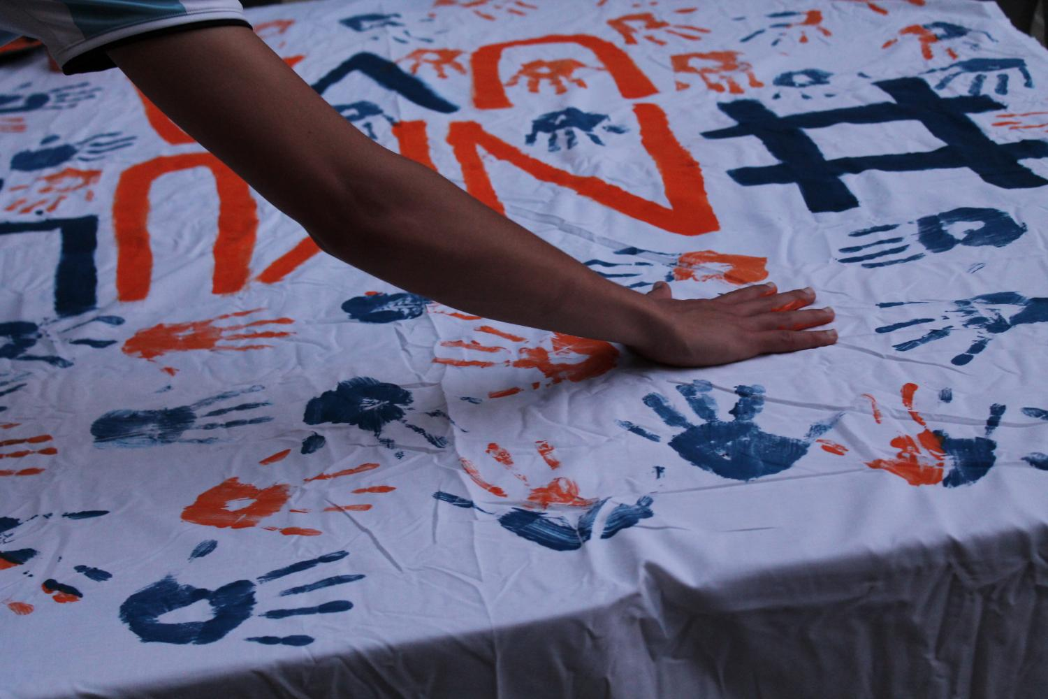 The banner will be sent to UVA in the coming weeks. After the vigil it was speckled with both hand prints and signatures.