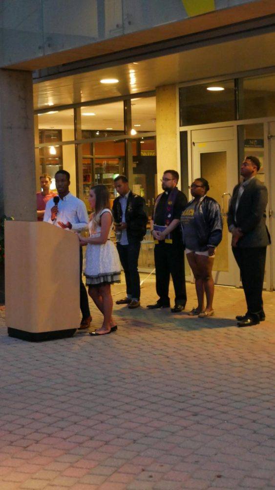 Speakers stood at a podium in the SU Plaza. SGA president Sami Dada and vice president Erica Bluford addressed a crowd upwards of 50.