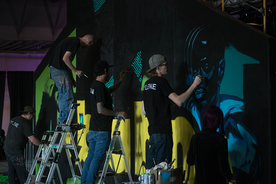 Artists+spray+paint+a+mural+of+the+Ubahn+Fest+2017+headliners.