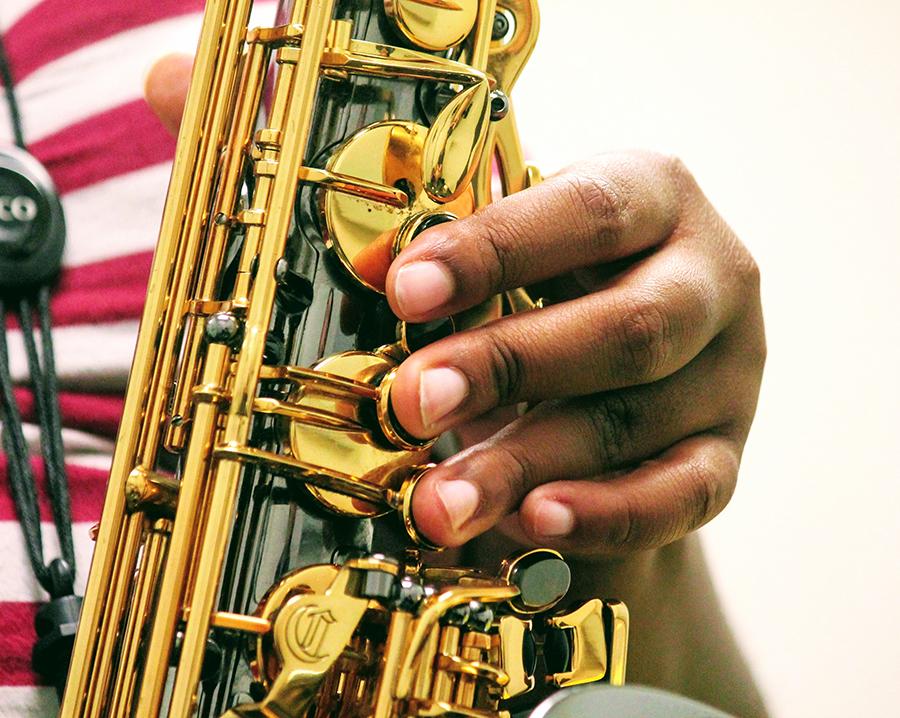 Kayla Upthegrove tinkers on her saxophone.